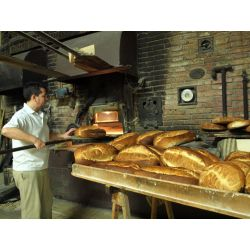 Panadero extrae pan del horno de leña